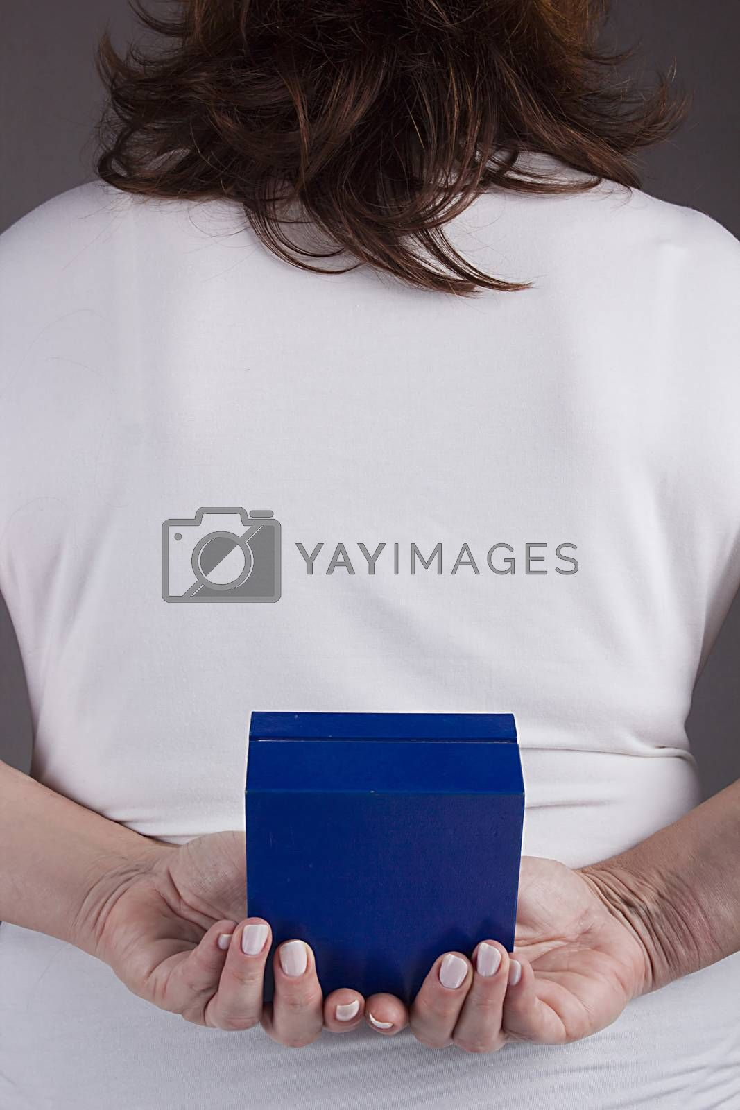 Woman with a gift behind her back on a gray background