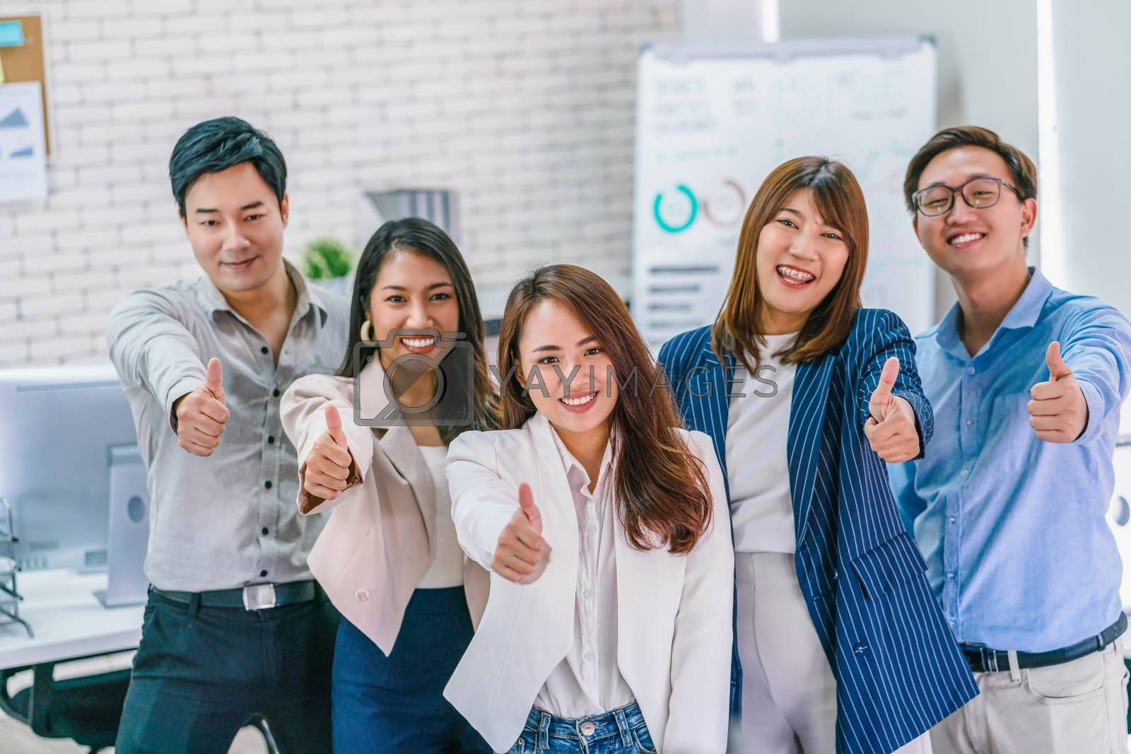 Group of Asian Business people showing thumbs up and looking at camera together at modern workplace, Team work and team building, small business owner and partnership, approve and agree concept