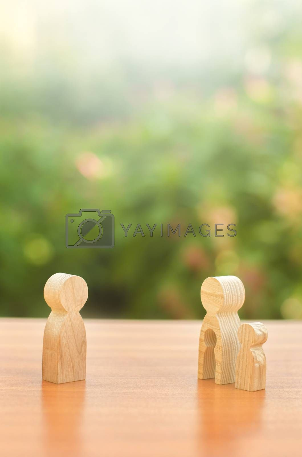 Wooden figures of a mother with a child stands apart from the father. Deprivation of parental rights. The child stay with the mother. Conflict resolution in court. Protection of mother s rights