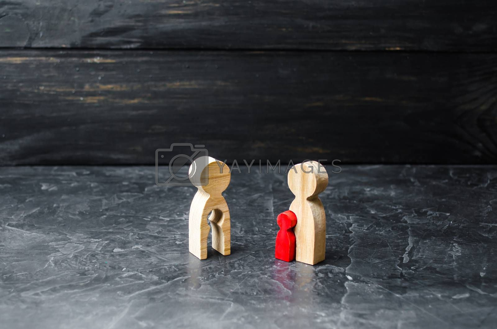 Wooden figurine of a mother with a void in the shape of a rchild looks with envy at the mother with the red child. Steal the baby. Adoption of children. futility, the desire to have children.