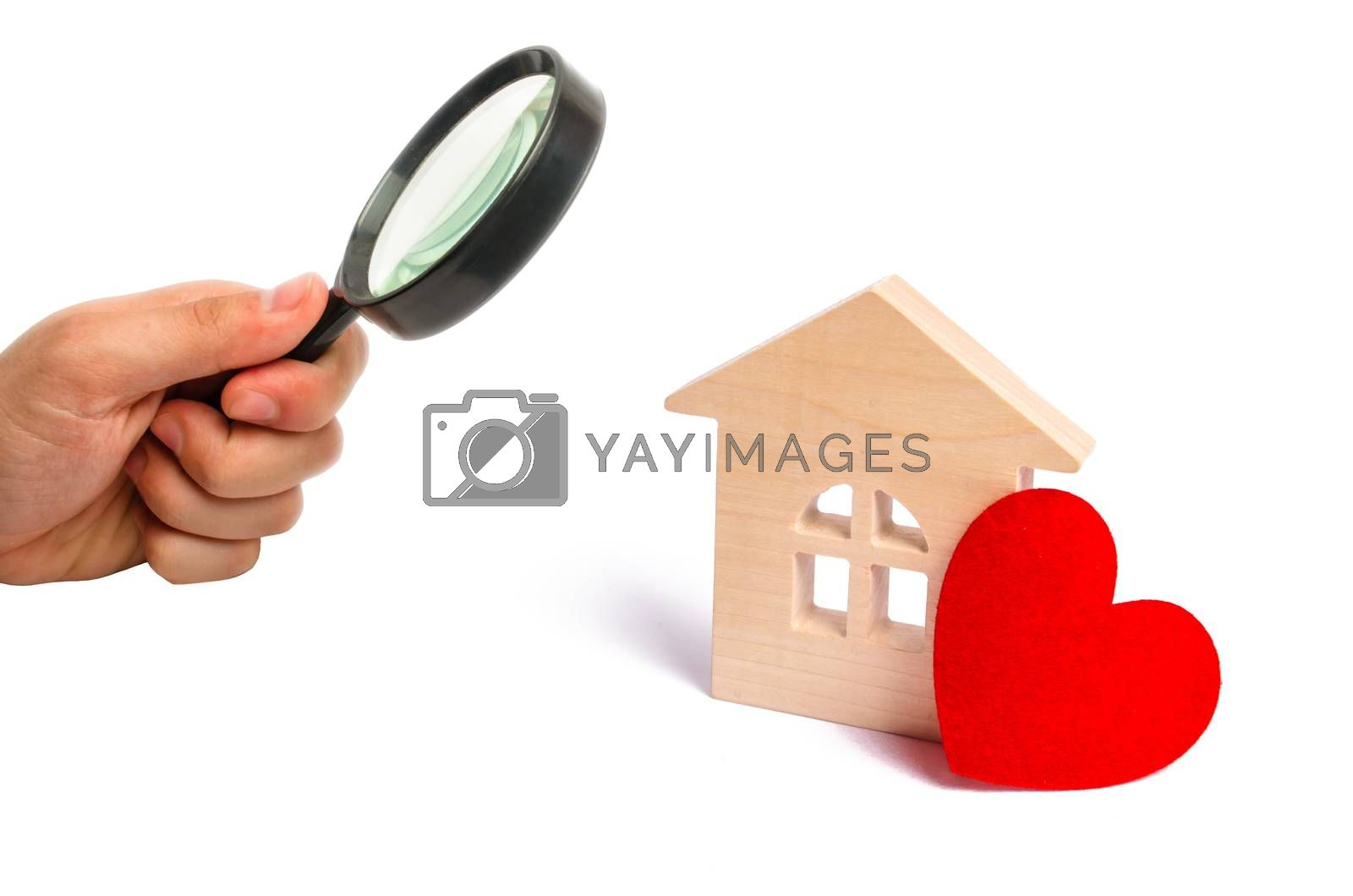 Magnifying glass is looking at the Wooden house with a red heart on a white background. Affordable housing. Family psychology. Love nest, love relationships. Buying a house with a young family.