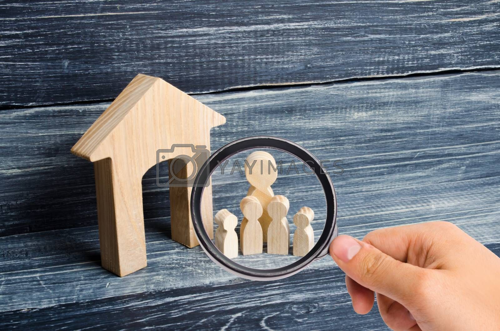 Magnifying glass is looking at the Big family is standing near the house. Wooden figures of persons stand near a wooden house. The concept of a couple in love, cohabitants, parents, buyers and sellers