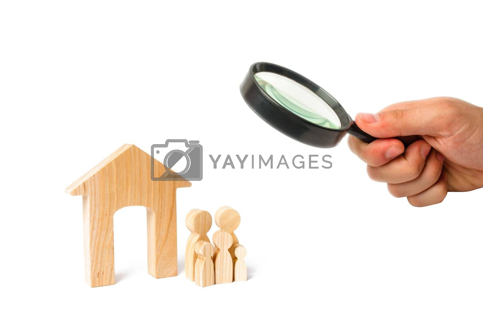 Magnifying glass is looking at the young family with children is standing near a wooden house. concept of a strong family, the continuation of the family. Loans for the purchase of affordable housing