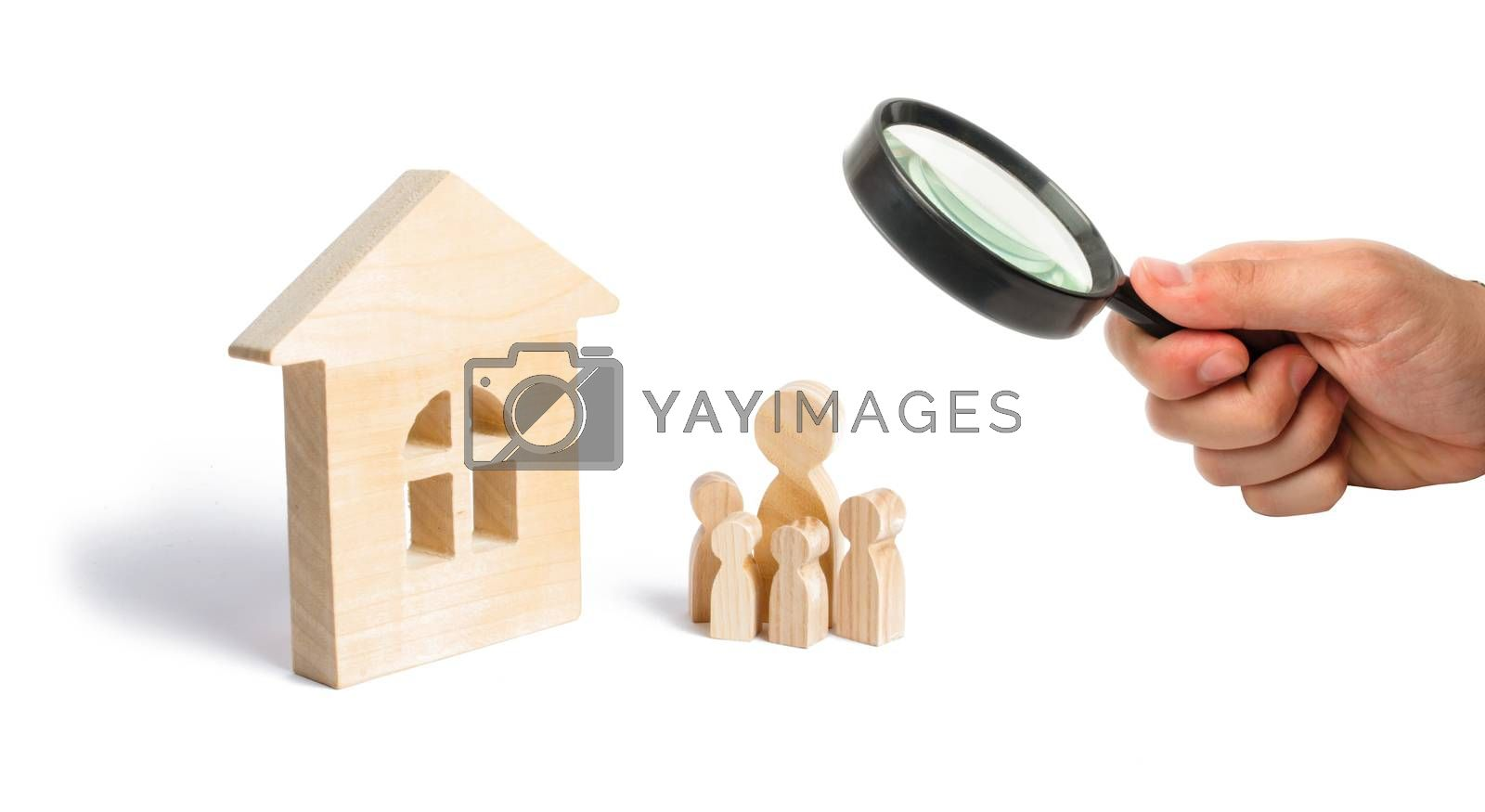 Magnifying glass is looking at the young family with children is standing near a wooden house. concept of a strong family, the continuation of the family. Loans for the purchase of affordable housing.