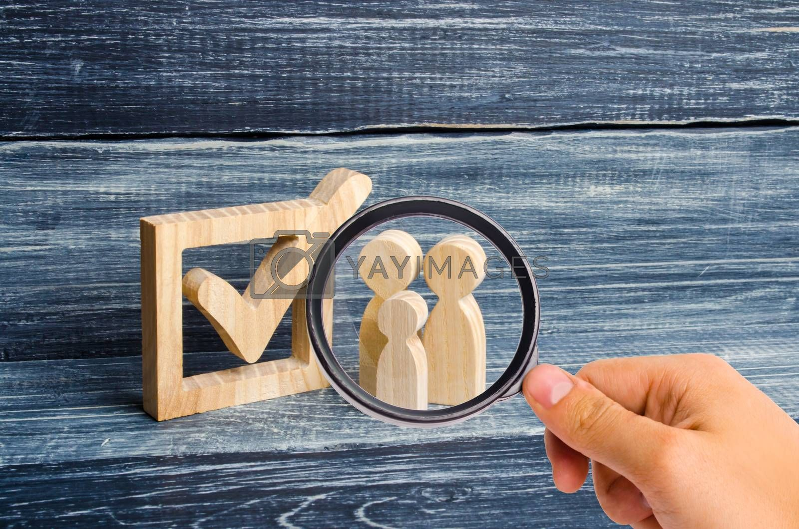 Magnifying glass is looking at the Three wooden human figures stand together next to a tick in the box. The concept of elections and social technologies. Volunteers, parties, candidates Human rights