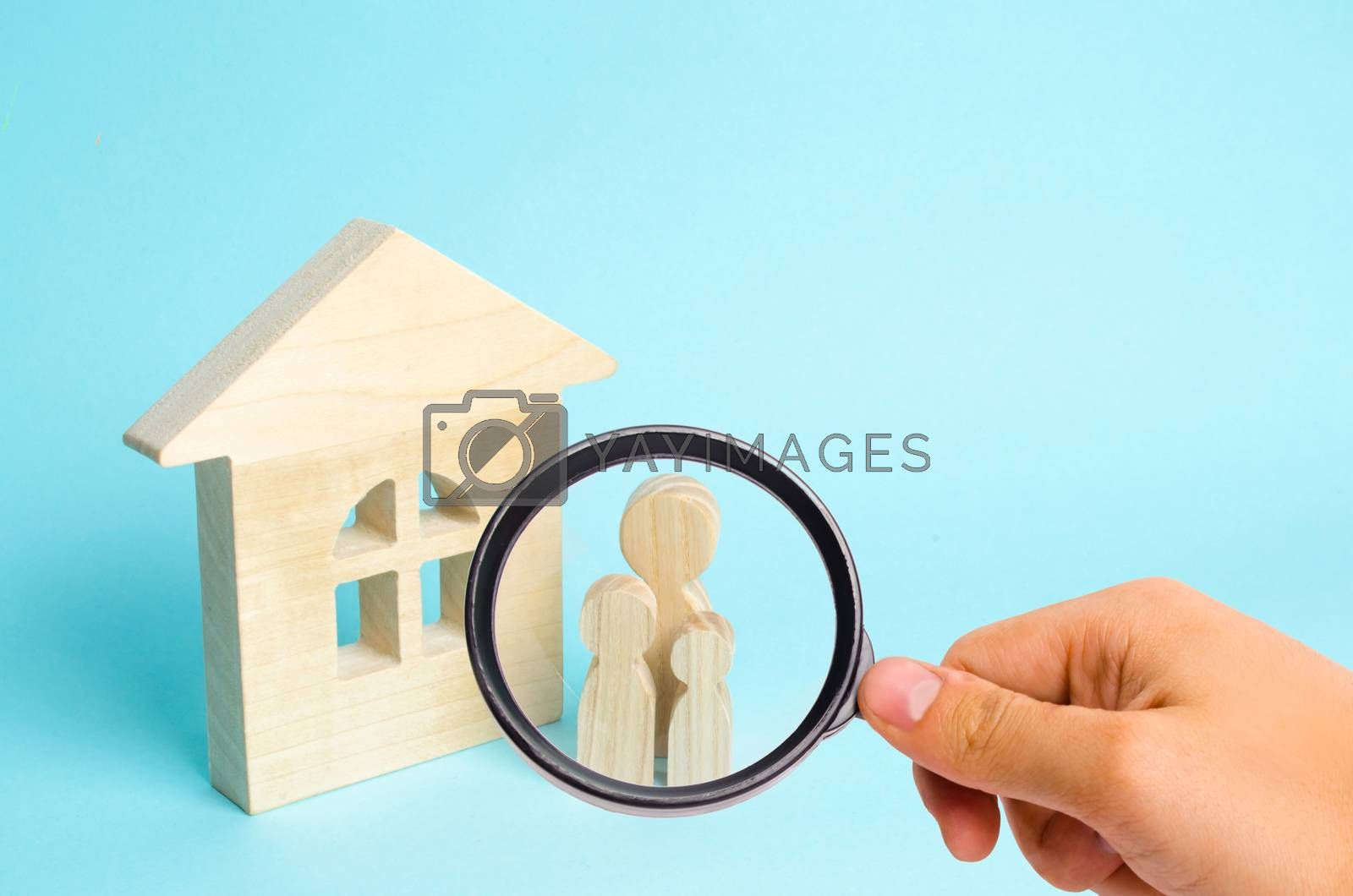 Magnifying glass is looking at the Family is standing near the house. Wooden figures of persons stand near a wooden house. The concept of a couple in love, cohabitants, parents, buyers and sellers