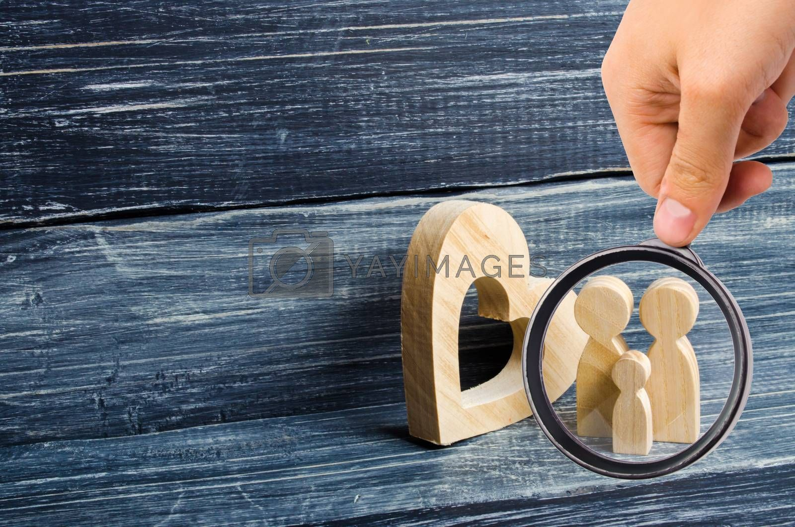 Magnifying glass is looking at the young family with a child is standing near a wooden heart. Love and loyalty, a strong young family. Family relationships. Civil marriage. Love, affection, sympathy