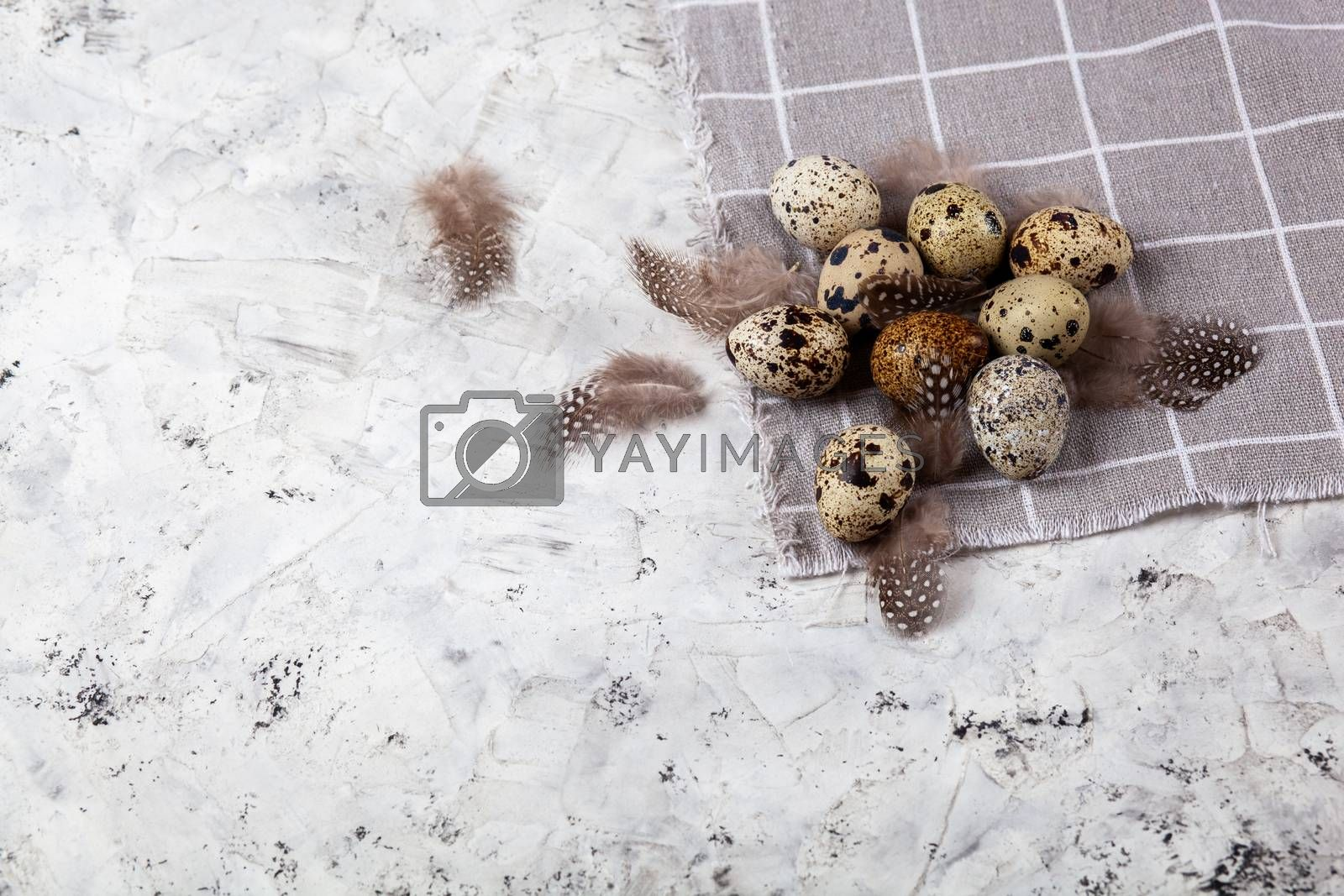 pile of Easter quail eggs on gray fabric rag on concrete background by Polina Tuliakova