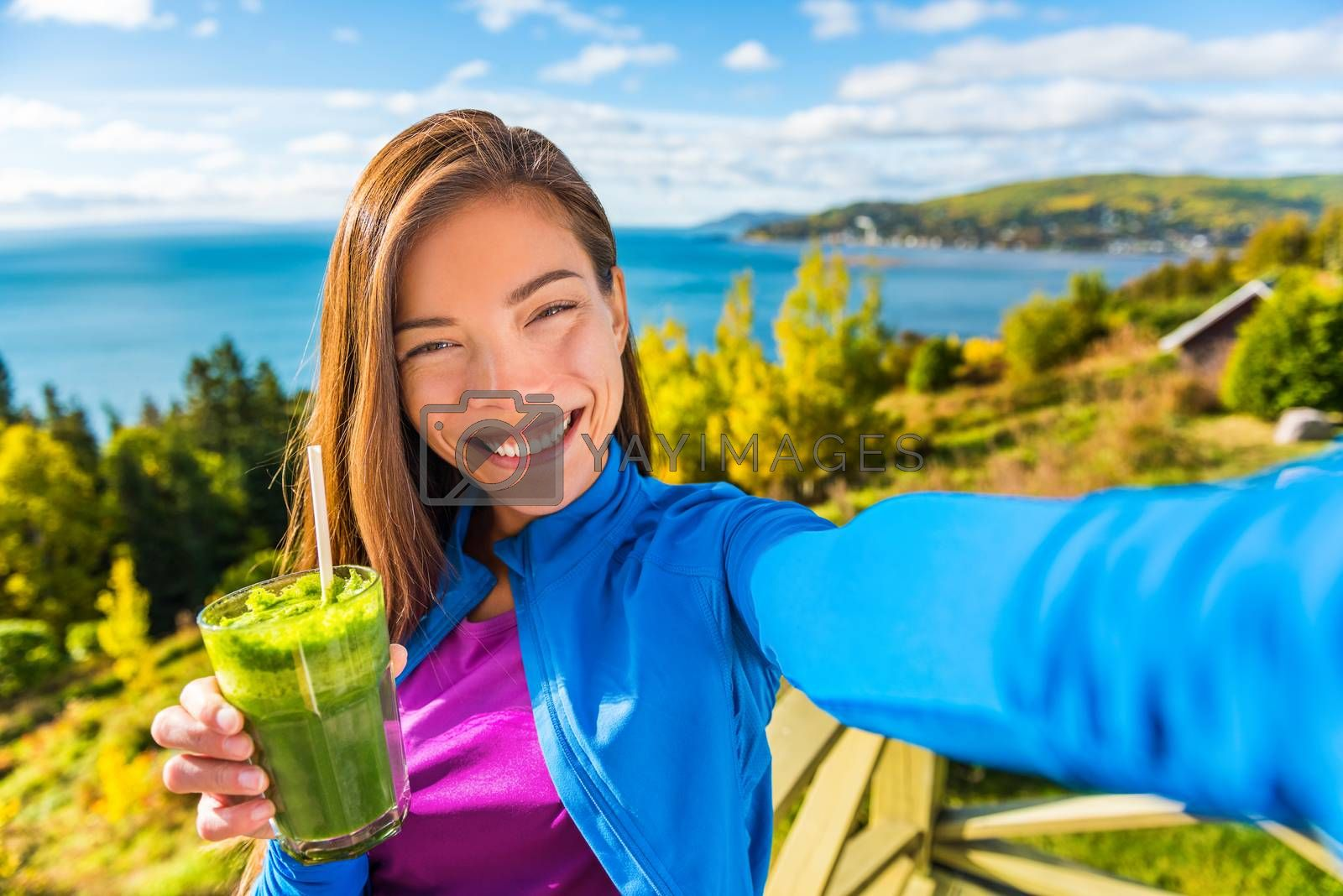Healthy green smoothie juice drinking selfie girl taking picture clean food diet healthy nutrition. Asian woman eating fresh spinach vegetable juicing in beautiful outdoors autumn nature by Maridav