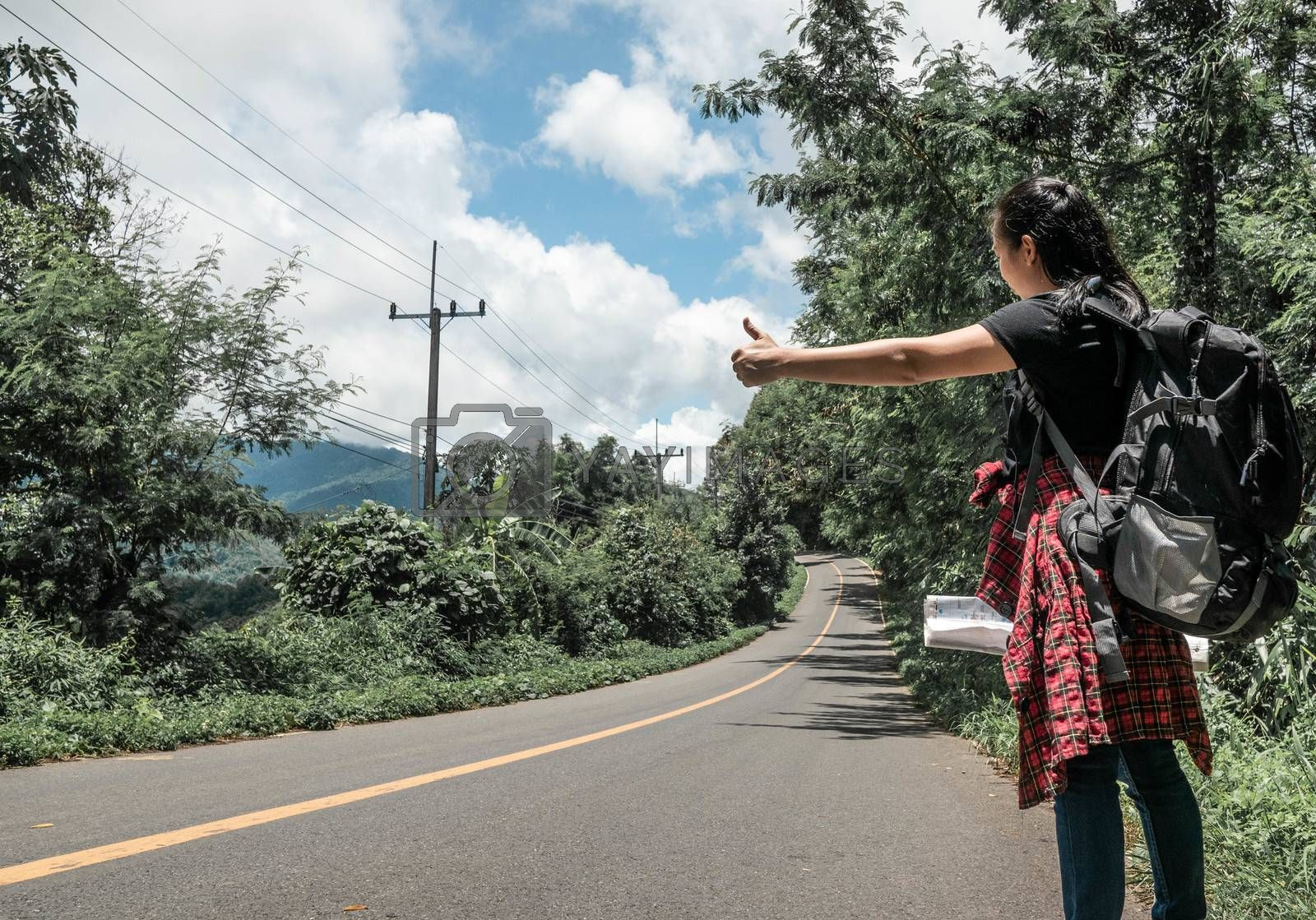 Travel woman backpacking hitchhiking by the road during summer vacation trip in amazing landscape nature in Thailand. Traveling and hitchhiking concepts.