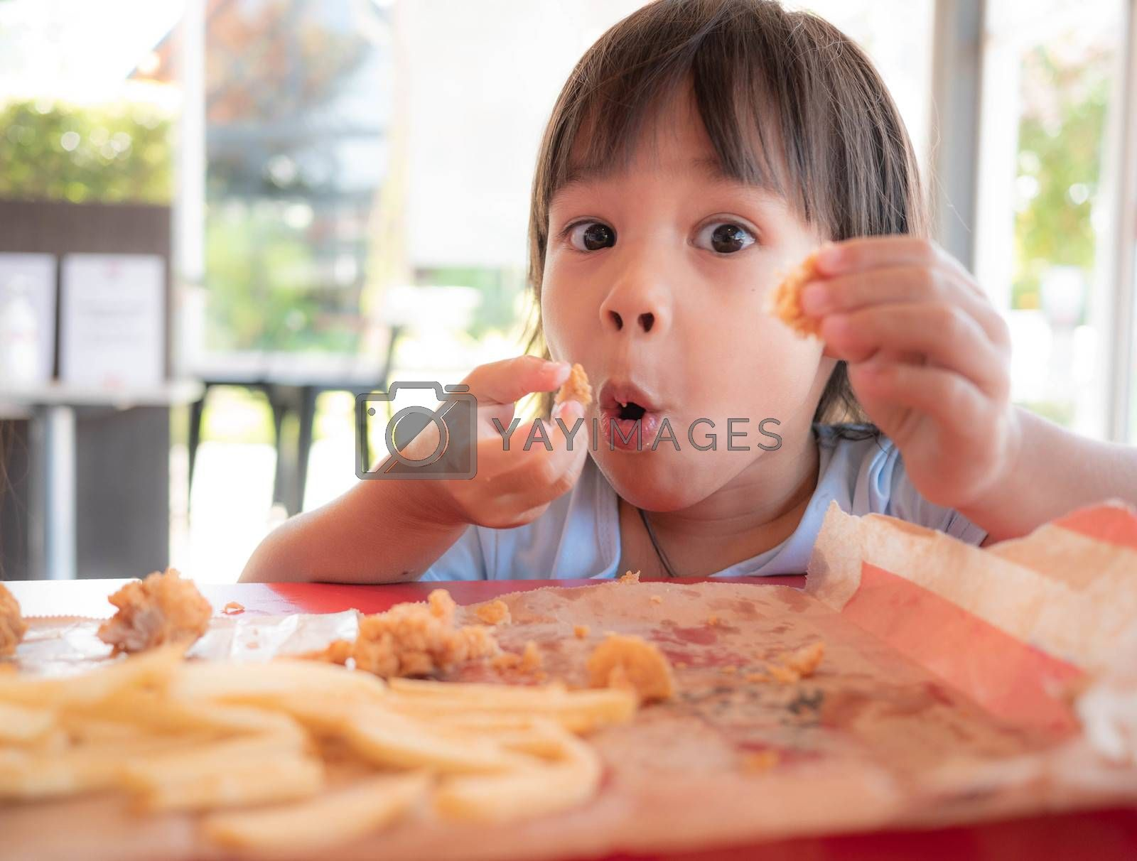 Asian little child girl enjoying with eating fried chicken and French fries in service shop. Junk food and Health concepts.