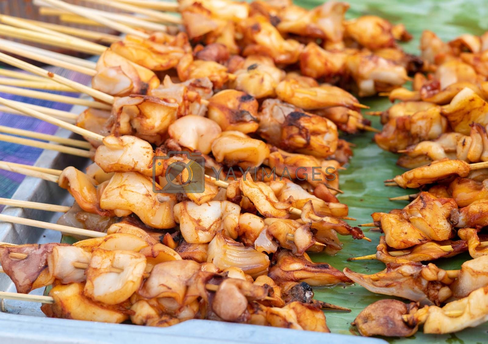 Squid skewers waiting to be grilled in charcoal grill. Thai delicious street food in local market.