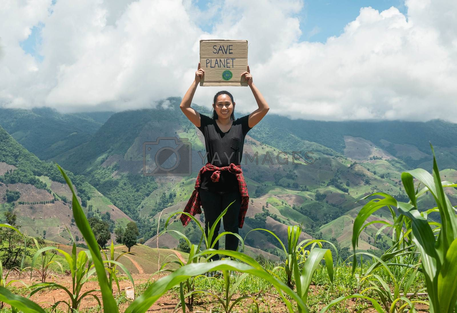 "Young woman holding ""Save the planet"" Poster showing a sign protesting against plastic pollution over the nature background. The concept of World Environment Day. Zero waste."