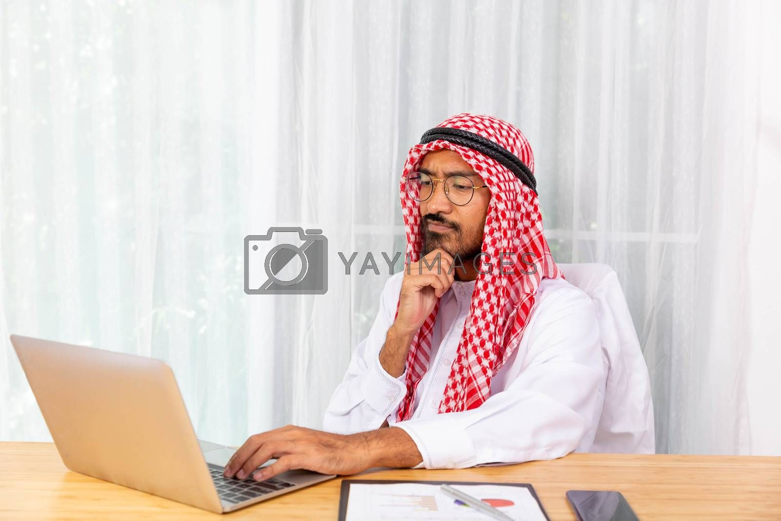 Arabian businessman is focus on his work in his office with computer notebook and mobile phone