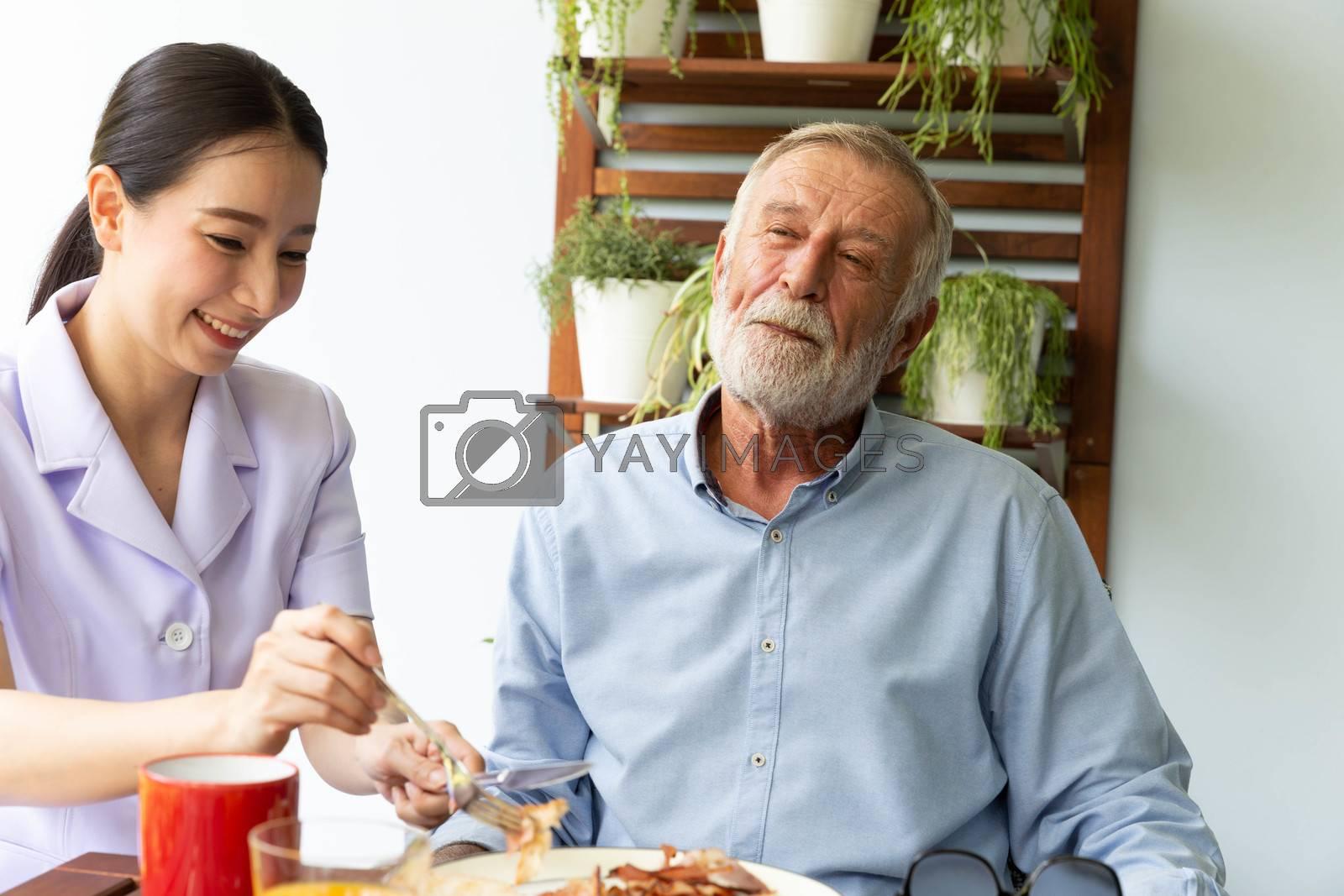 Asian nurse assist happy senior retirement man having breakfast together