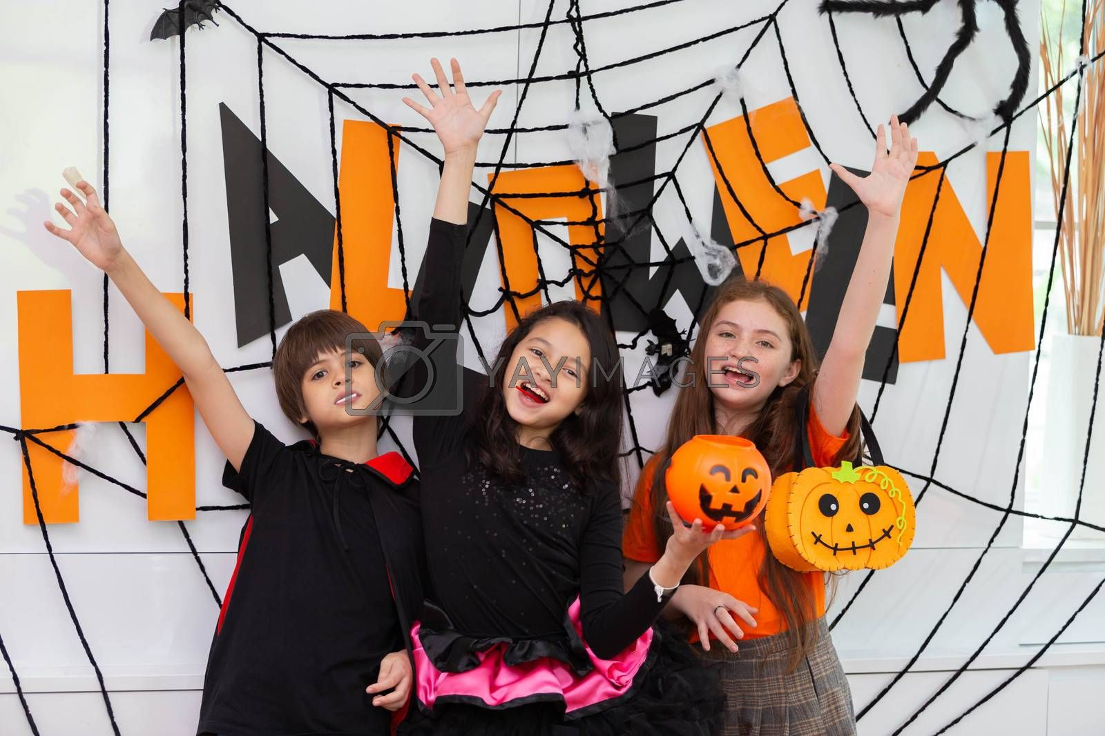 Happy Halloween by a group of children, brother and sister in carnival costume in decorated house