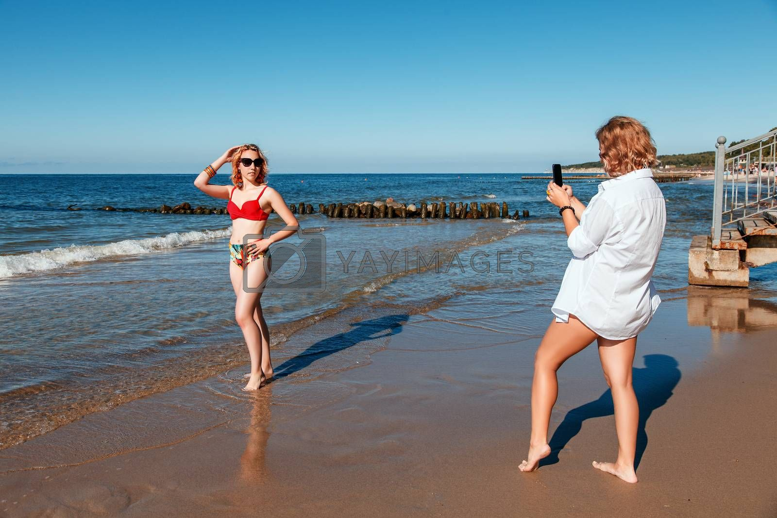 two girls in swimsuits take pictures of each other with smartphones on the seashore on sunny summer day