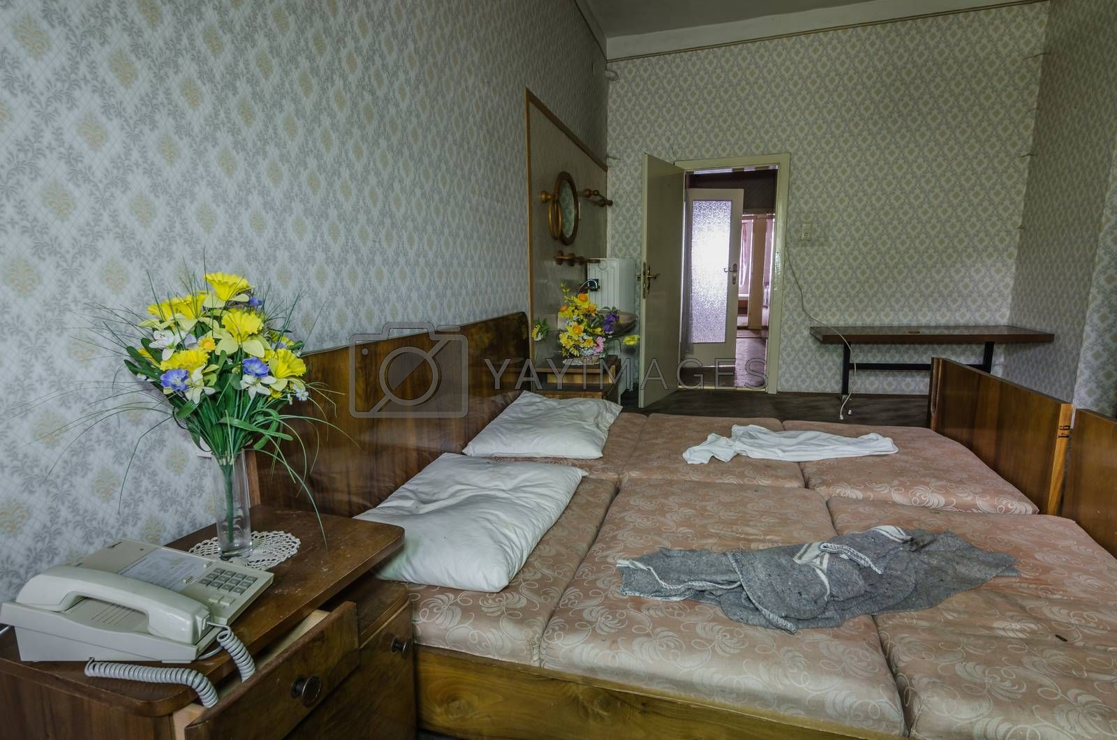yellow flowers near a bed in hotel room by thomaseder