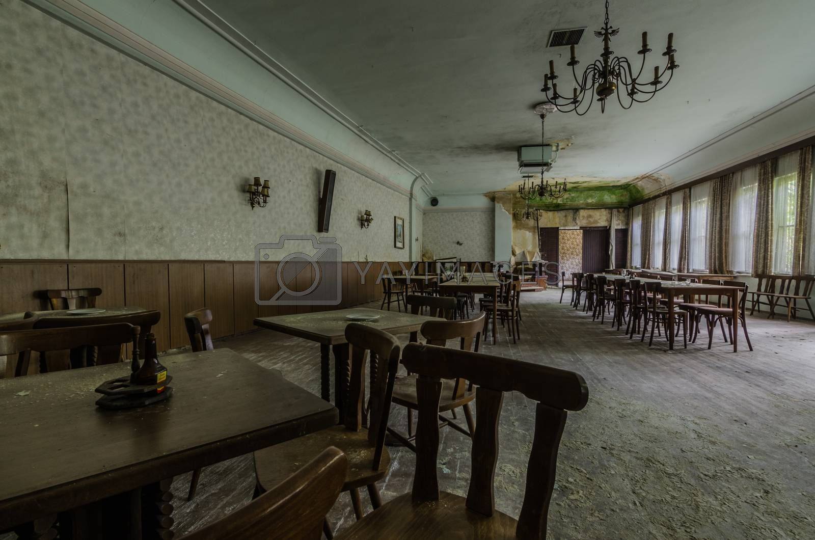 abandoned ballroom with tables and armchairs in a guest house