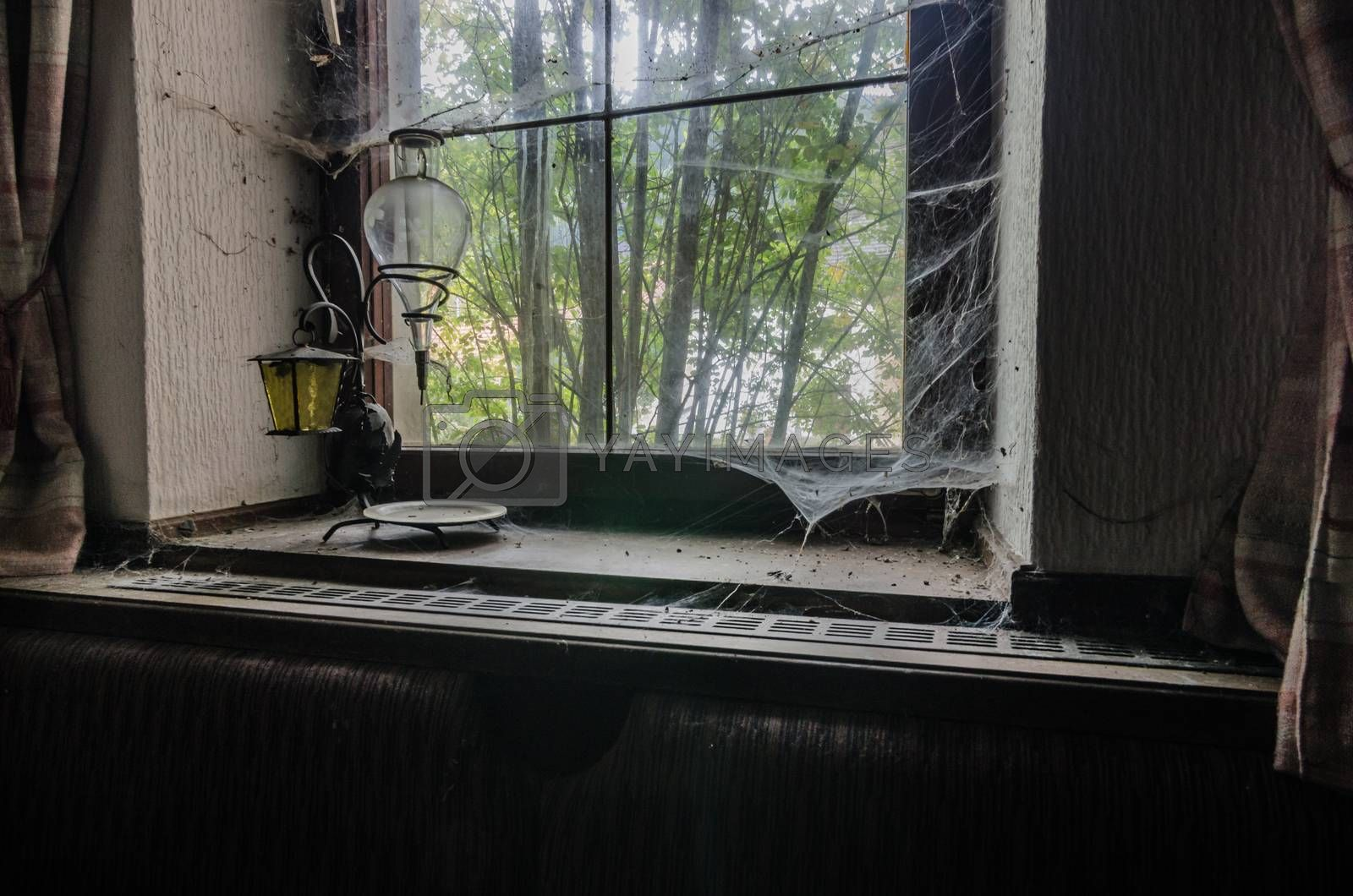 Old lamp on a windowsill with cobwebs