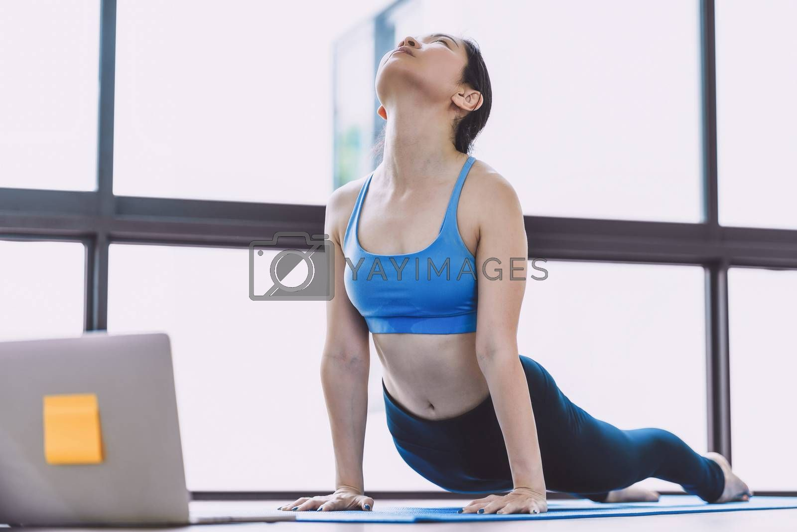 Asian woman practicing yoga from home with laptop when Covid19 o by Tzido