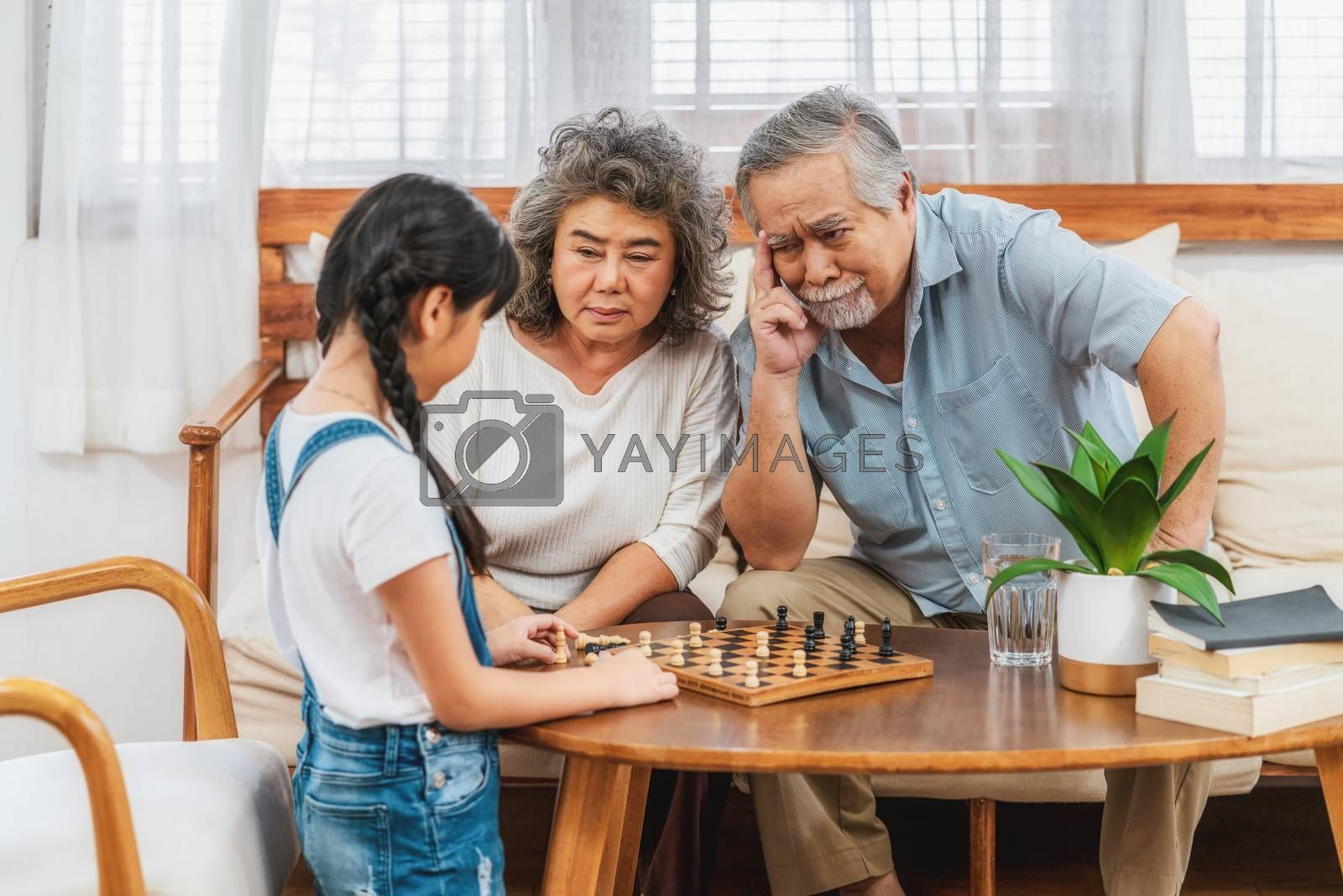 Asian couple Grandparent with grandchild playing the chess with Use thought together, support and success, Long live and Elderly society,Warm family and happiness,social distancing concept
