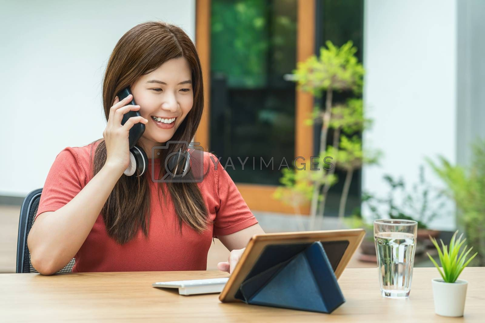 Asian business woman using mobile phone with keyboard and calling for working from home in outdoor home and garden, startups and business owner, social distance and self responsibility