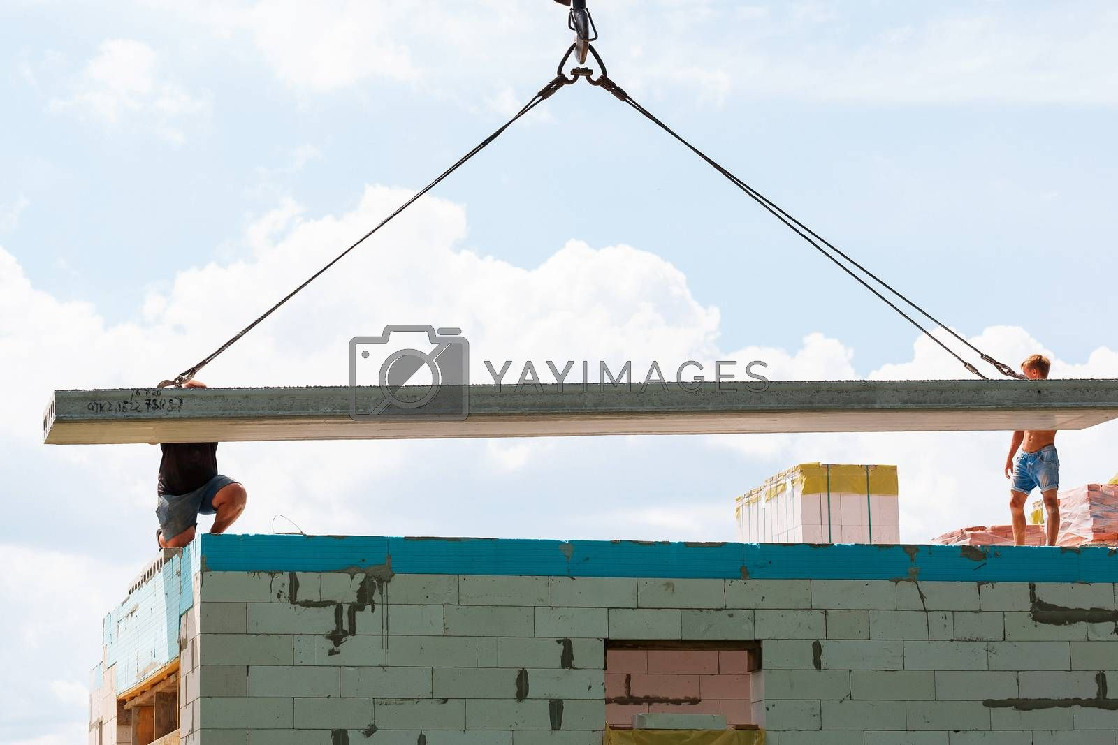Builder worker installing concrete floor slab panel at building construction site by Len44ik