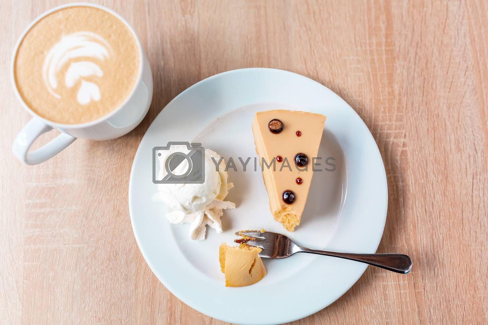 A piece of caramel cheesecake served with ice cream and a cup of cafe latte, flat lay