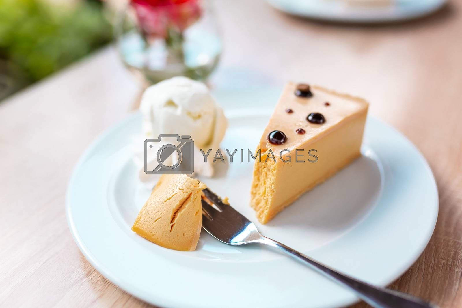 A piece of delicious caramel cheesecake served with ice cream and flowers on the table