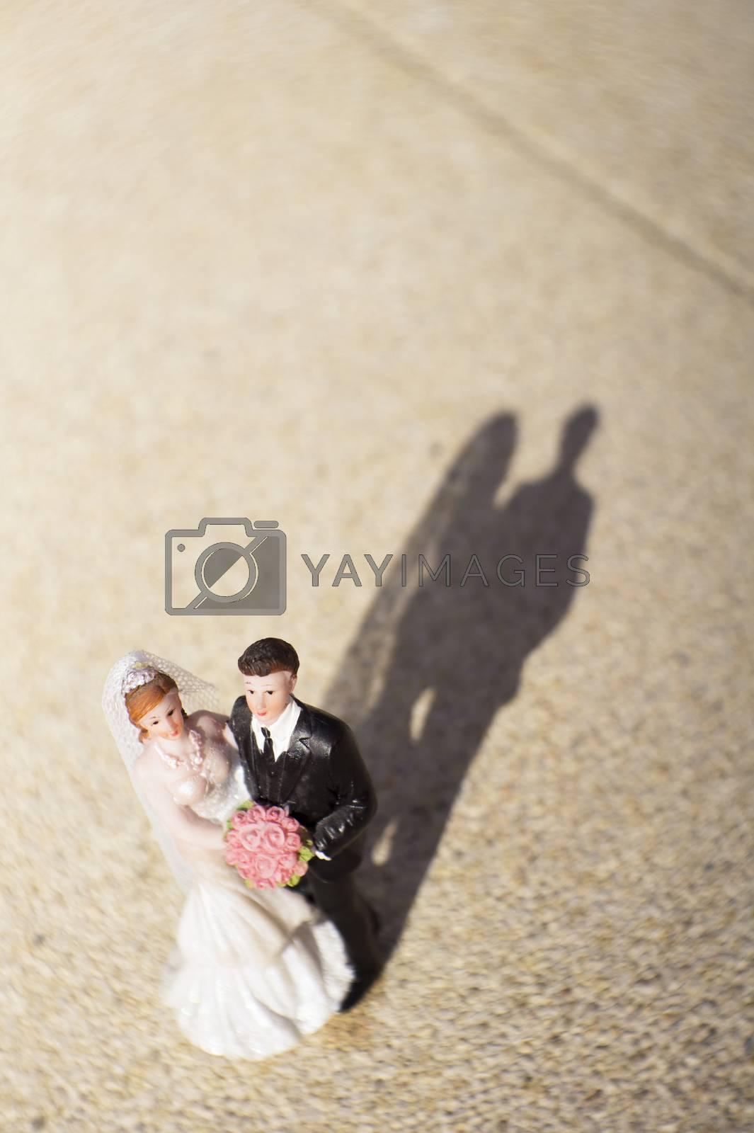 Standard figure of wedding couple on beige floor. No people
