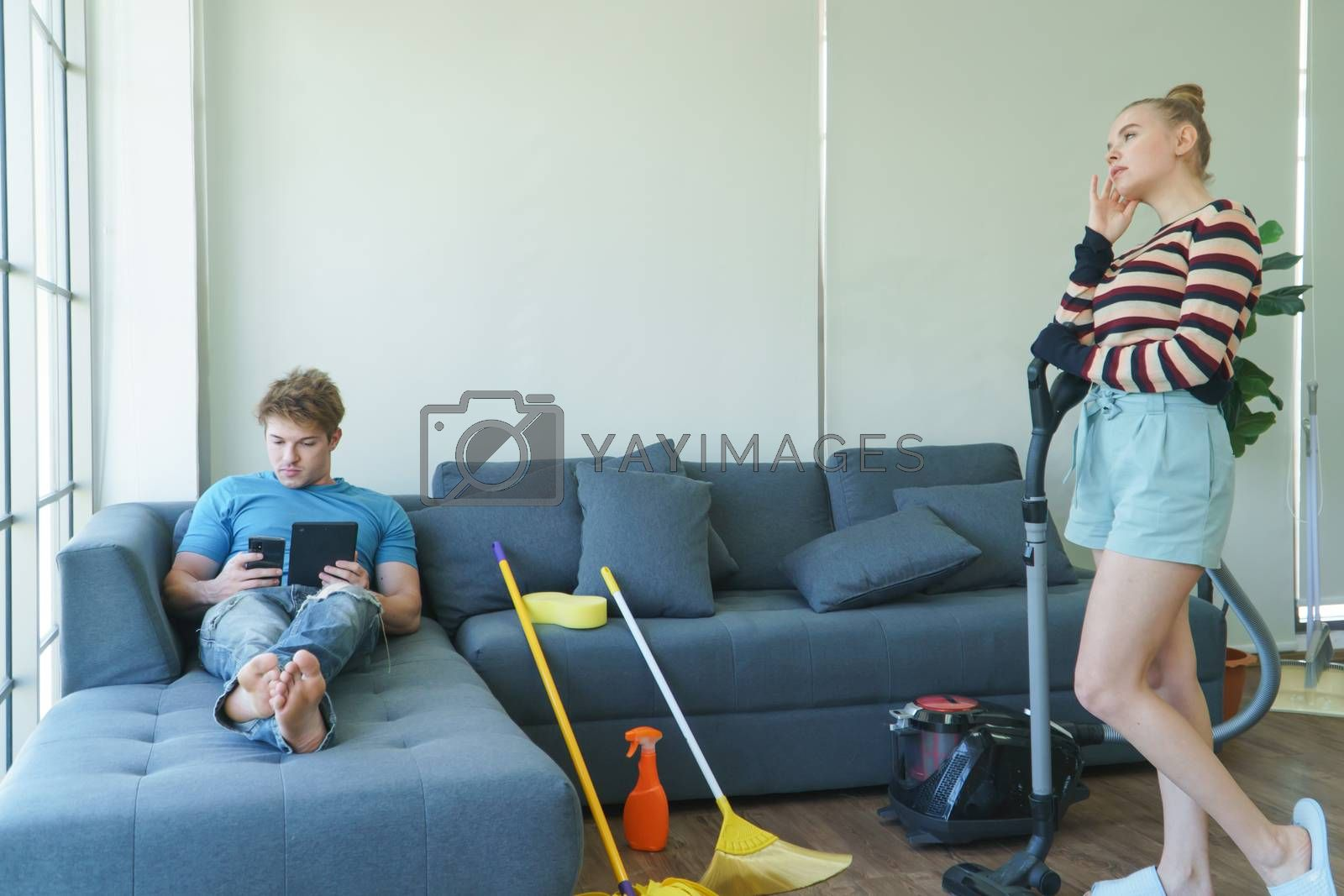 A young couple of Caucasian people do chores together. Beautiful women are cleaning the floor using vacuum cleaners. Handsome men are lazy to sleep and use tablets on the sofa.