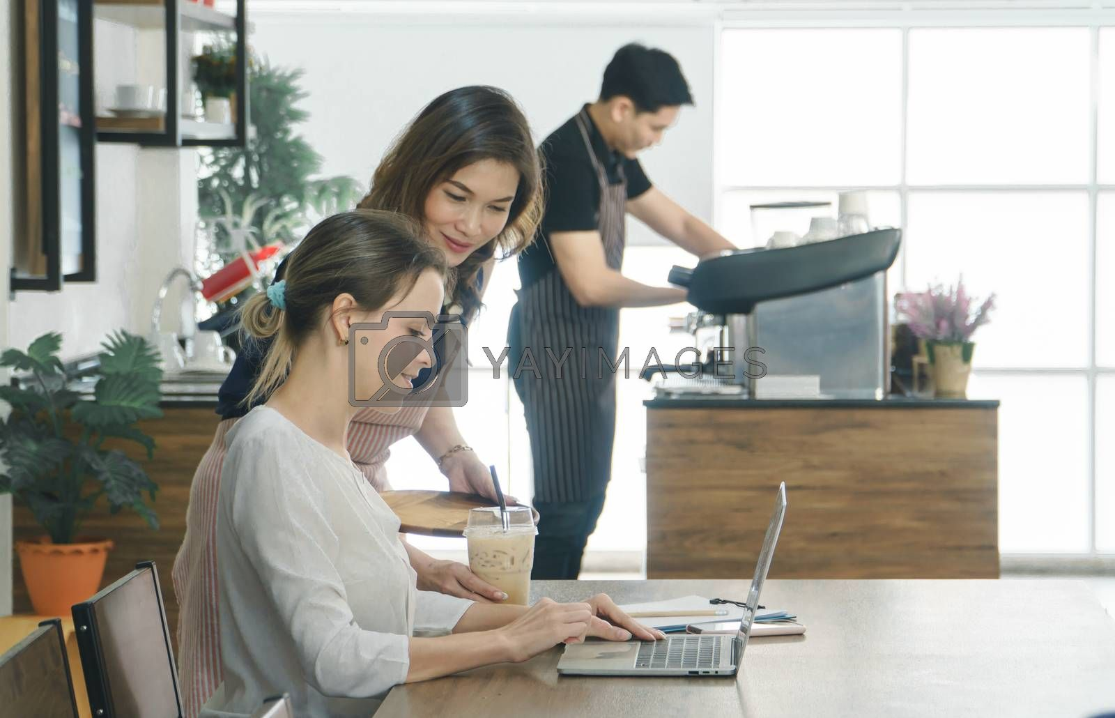 Beautiful young Caucasian women Using a laptop in the cafe. Asian female waitress serving espresso customers in a coffee shop. Background barista is preparing to make a drink according to order