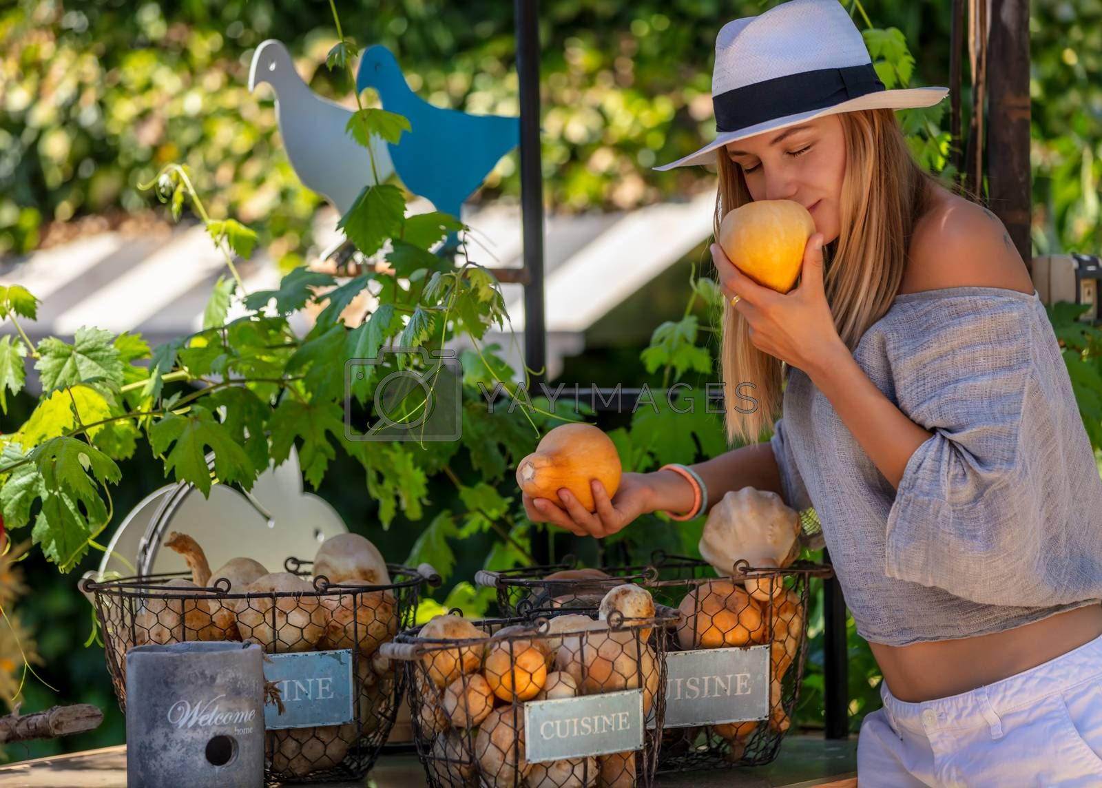 Happy Healthy Woman with Pleasure Spending Summer day at Outdoor Farmers Eco Market.  Enjoying Aroma of a Fresh Ripe Little Pumpkin. Vegetarian Nutrition. Healthy Lifestyle.