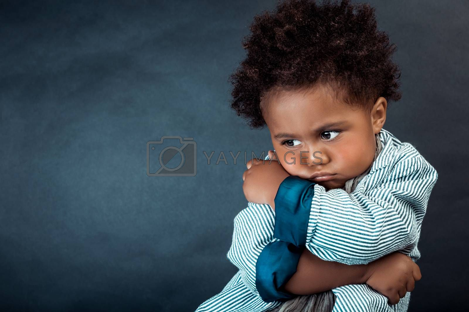 Portrait of a Little Cute Upset African-American Boy Over Dark Background. Baby Model. Unhappiness and Sadness Concept.