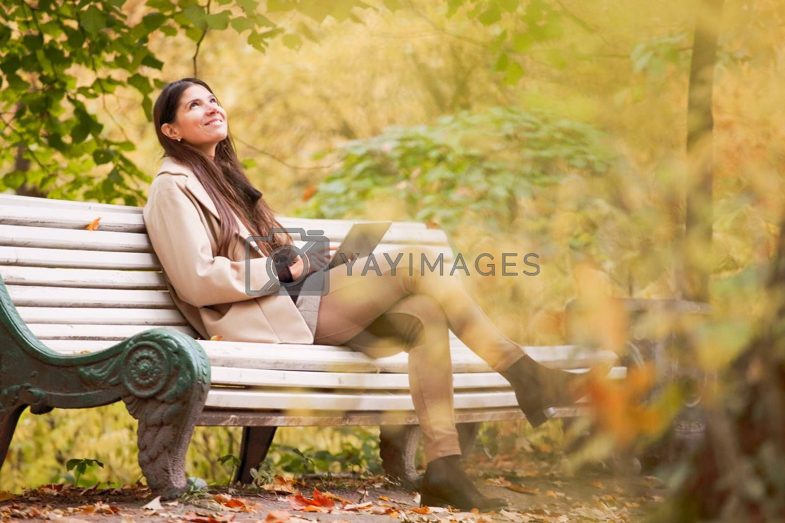 Smiling young woman using digital tablet sitting in autumn park