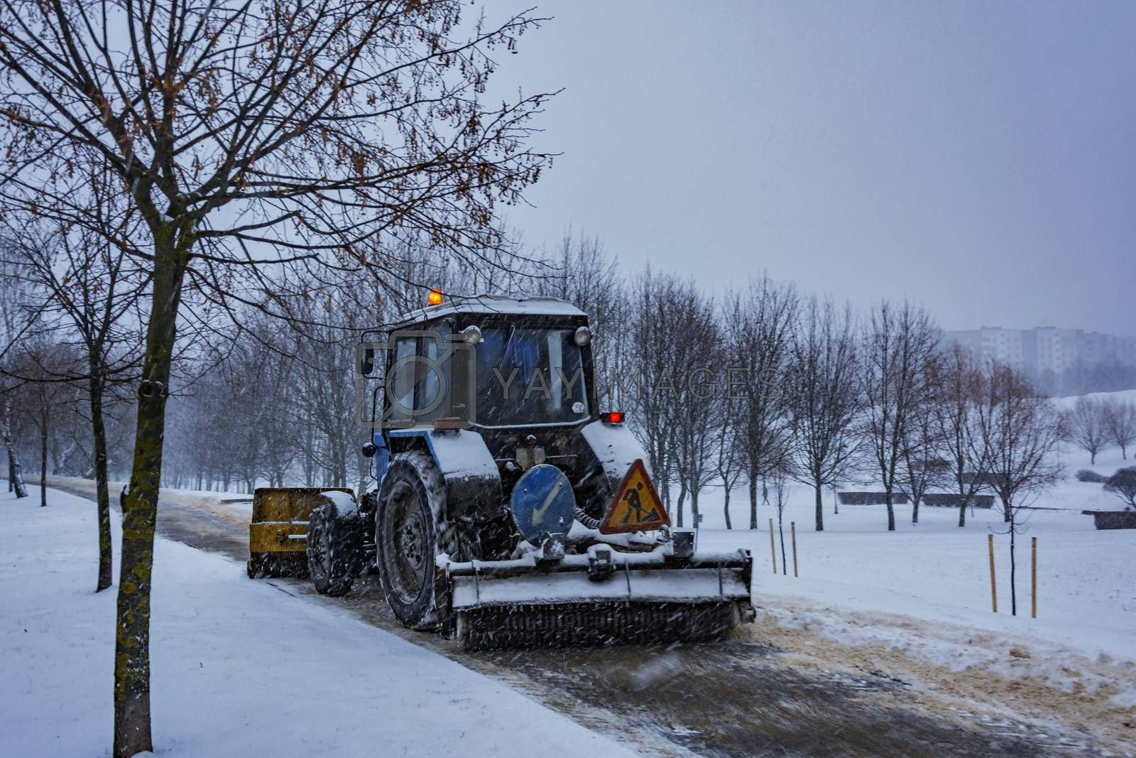 The tractor cleans snow from the sidewalk during snowfall by Grommik
