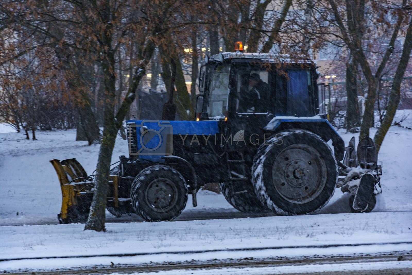Tractor Balorus cleans snow from the sidewalk during snowfall by Grommik