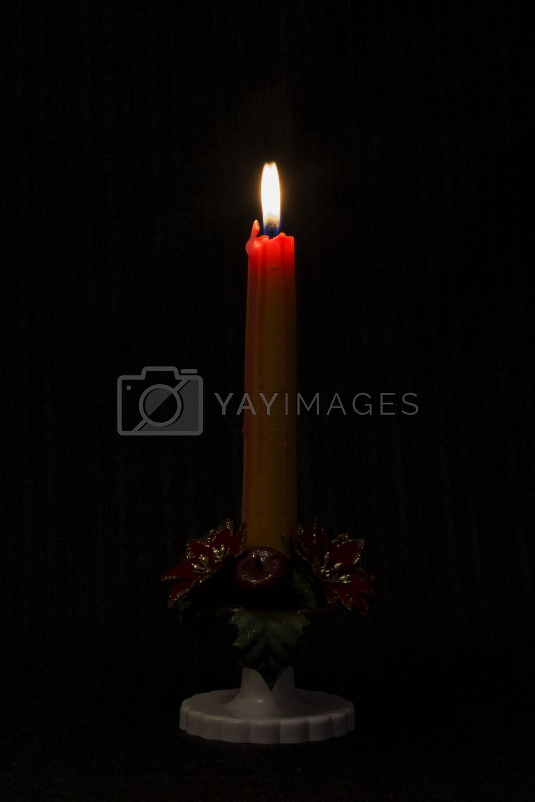 Lit candle on black background