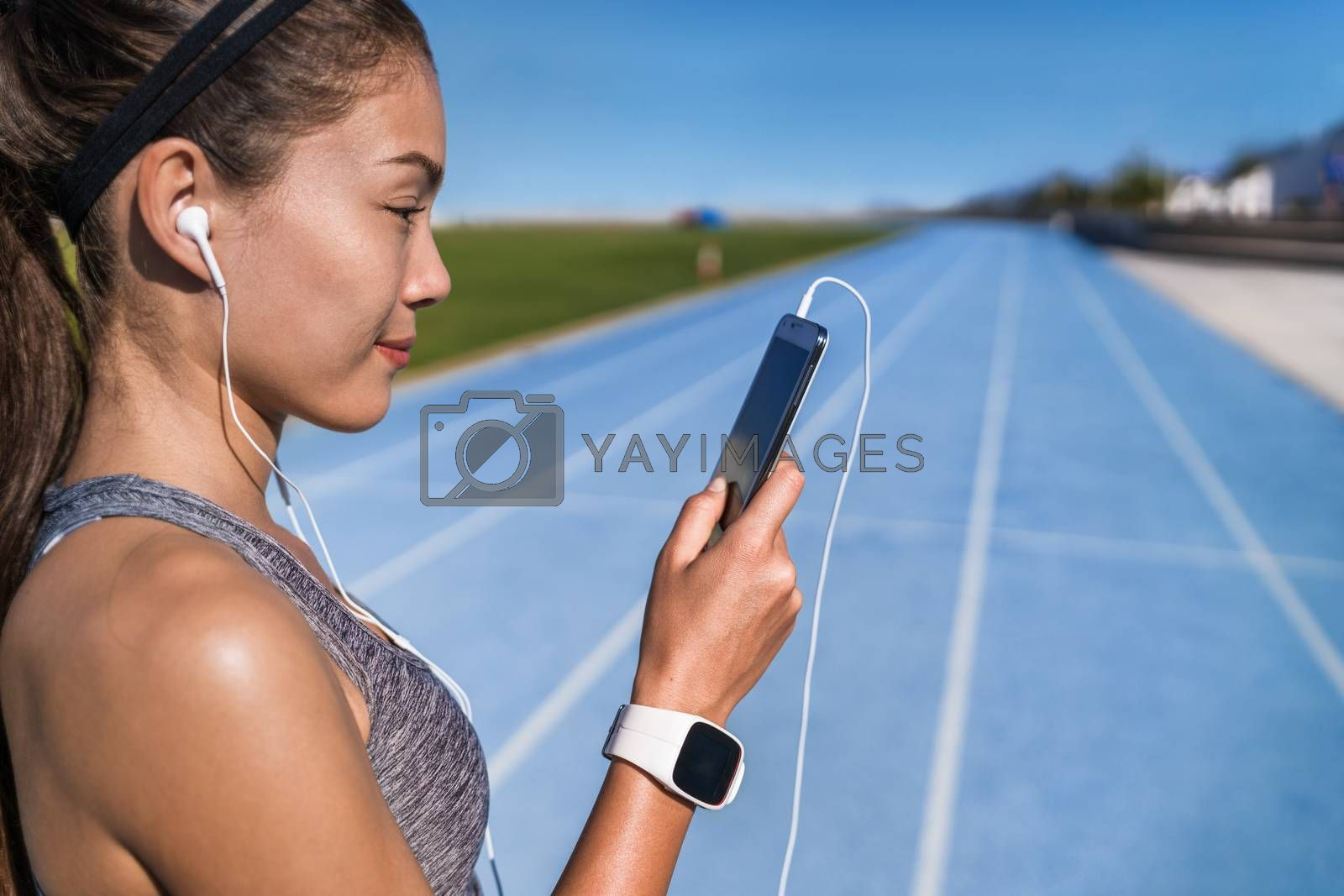 Running music motivation woman listening to phone app with headphones. Runner looking at smartphone on stadium running track with earphones and mobile phone ready to run. Healthy lifestyle.