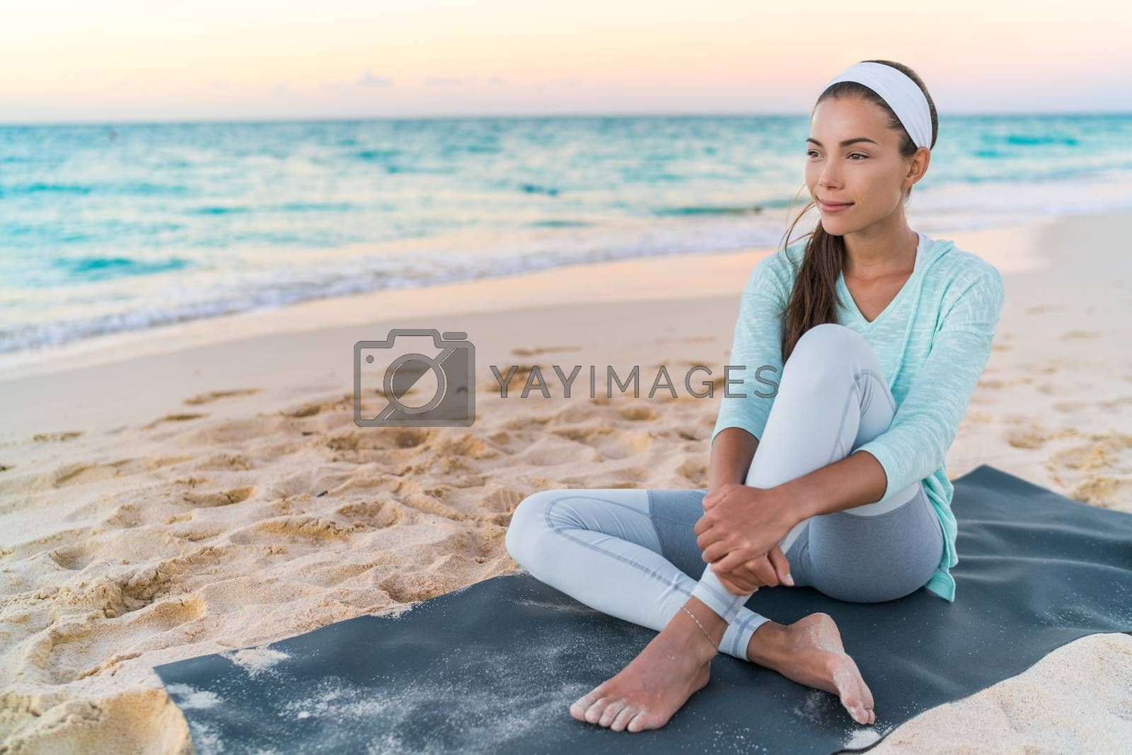 Yoga beach woman relaxing on fitness mat after workout. Fit Asian fitness athlete girl doing exercise in activewear at sunset or sunrise. Mindfulness healthy lifestyle.