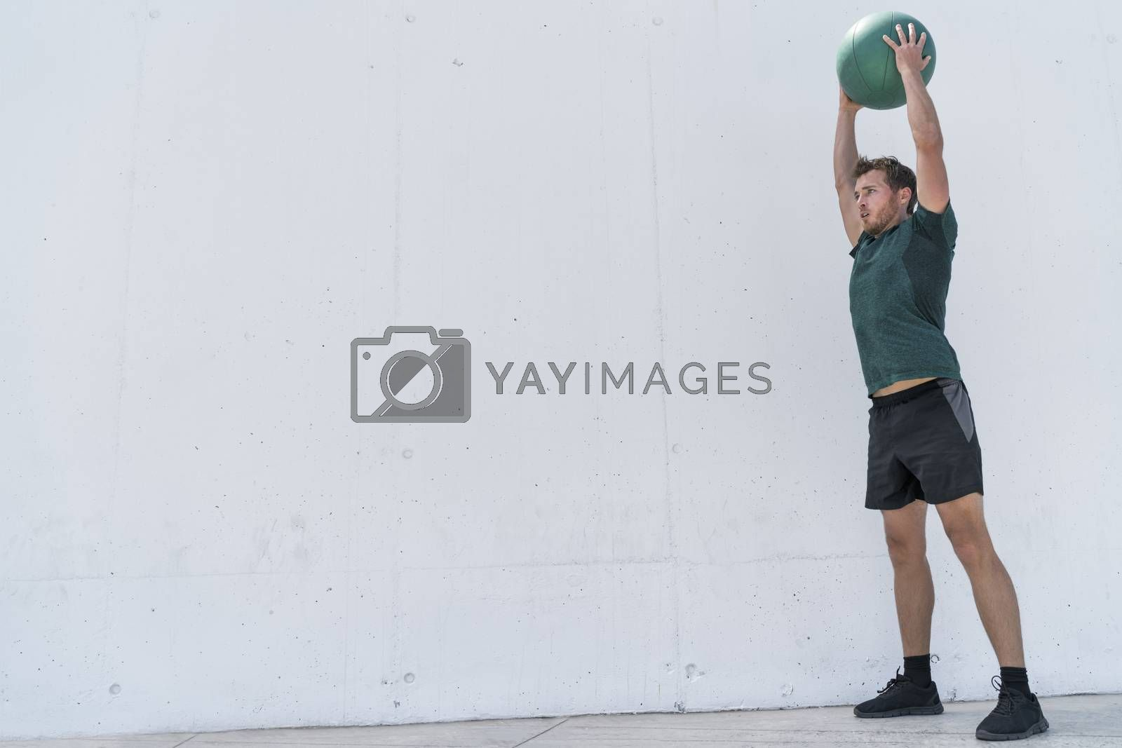 Fit man throwing medicine ball on floor workout by Maridav