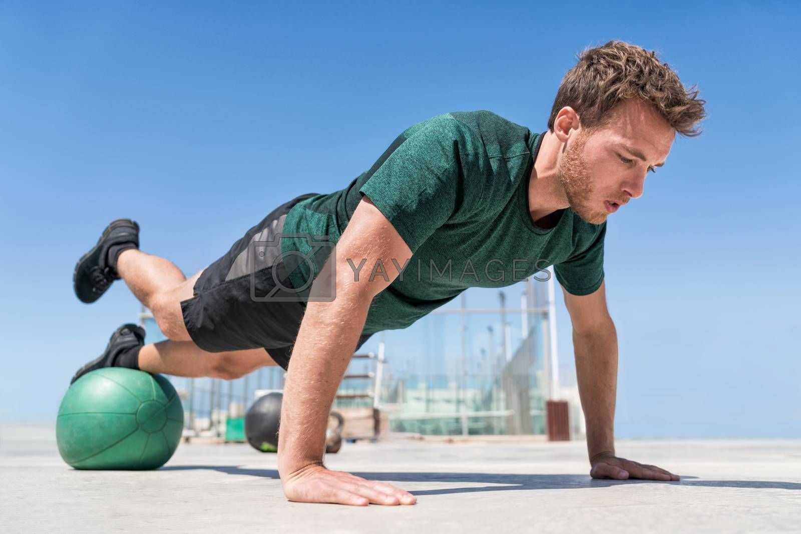 Man doing pushups balancing on medicine ball by Maridav