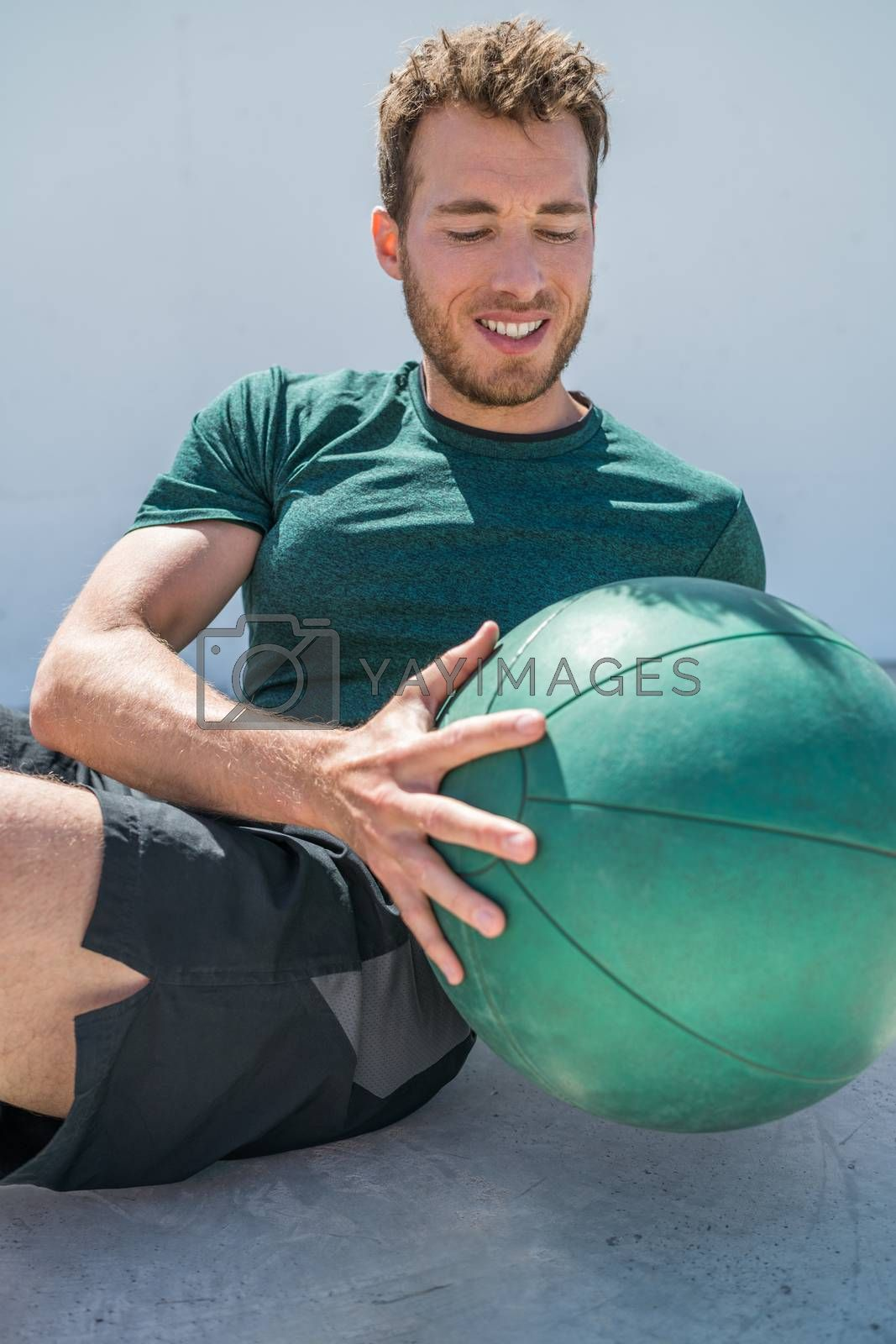 Gym workout with medicine ball exercise man doing russian twist exercises. Athlete working out doing exercises training oblique abs muscles on fitness centre floor.