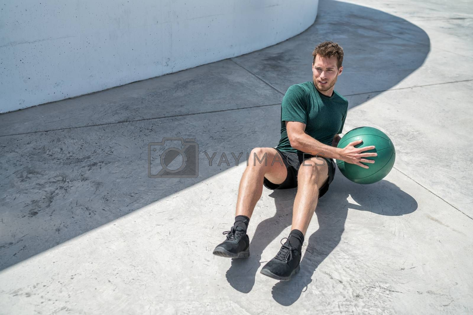 Medicine ball exercise russian twist man. Abs workout - fitness athlete working out doing exercises training oblique muscles on outdoor floor.