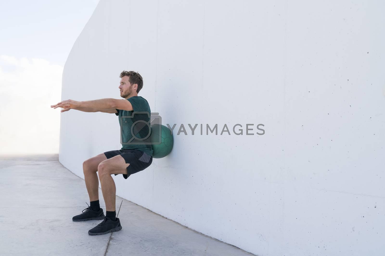 Strength training man doing medicine ball squats by Maridav