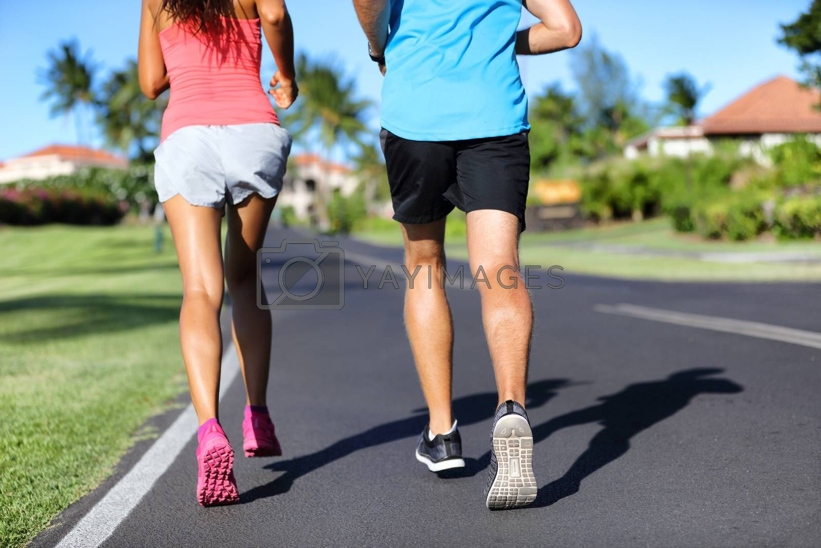 Runners running on road - closeup of legs of athletes sprinting training cardio together by Maridav