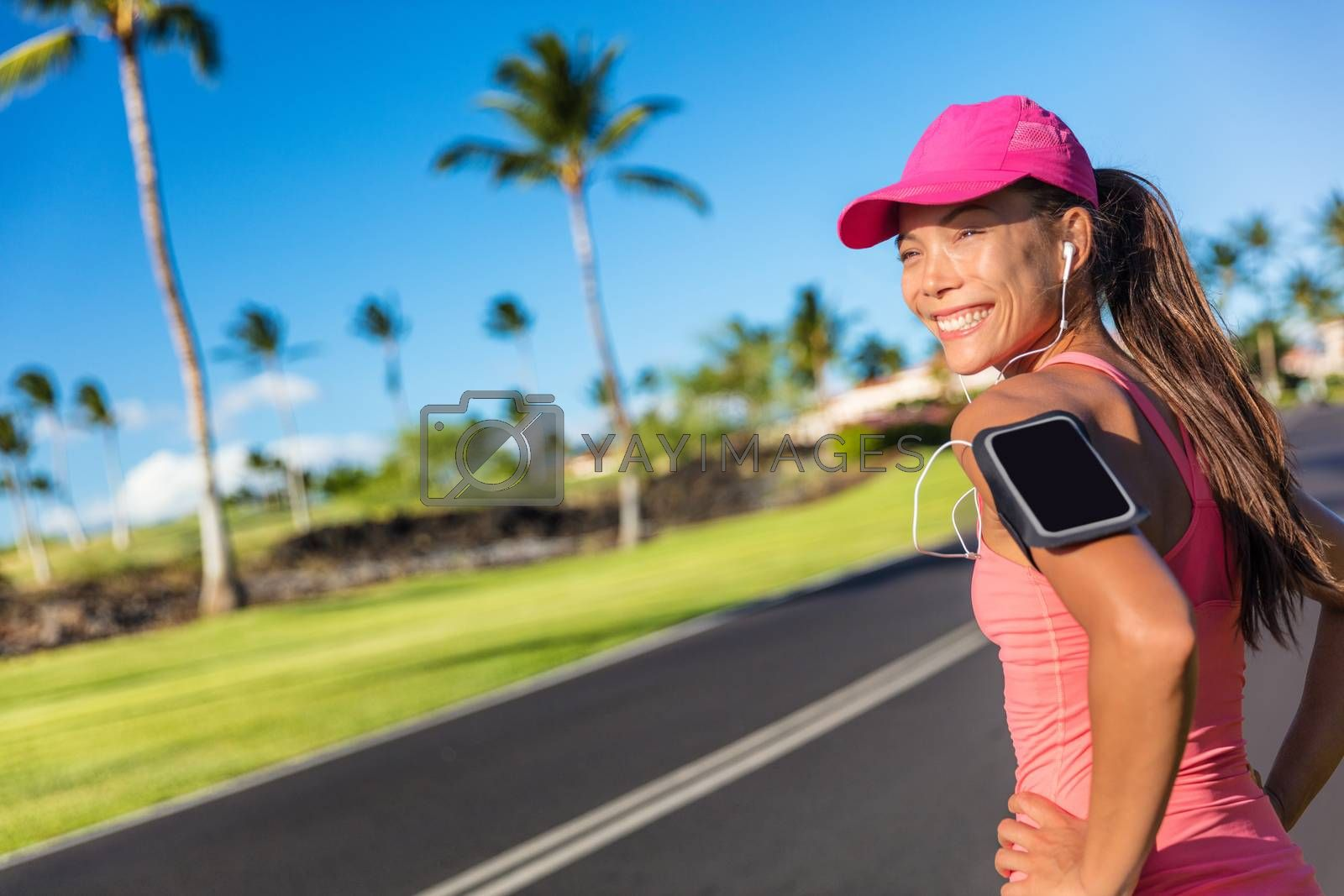 Fitness motivation running music woman runner. Happy jogging girl listening to smartphone app with earphones. Asian athlete wearing cap and armband smart phone holder outdoor on city road.