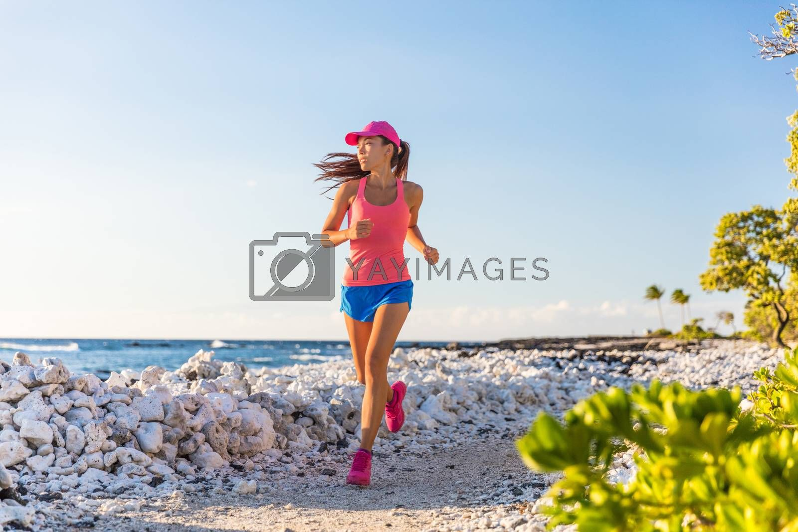 Healthy active runner girl running on beach trail path of coral rocks in Hawaii, morning training alone.