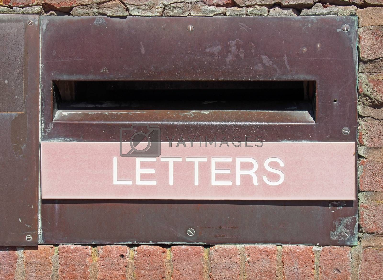 an old british postal mail box in a brick wall with rusted metal surround and the word letters on a faded red panel